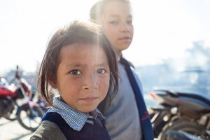A portrait of a young Nepali girl and her sister taken while they were walking home from school.