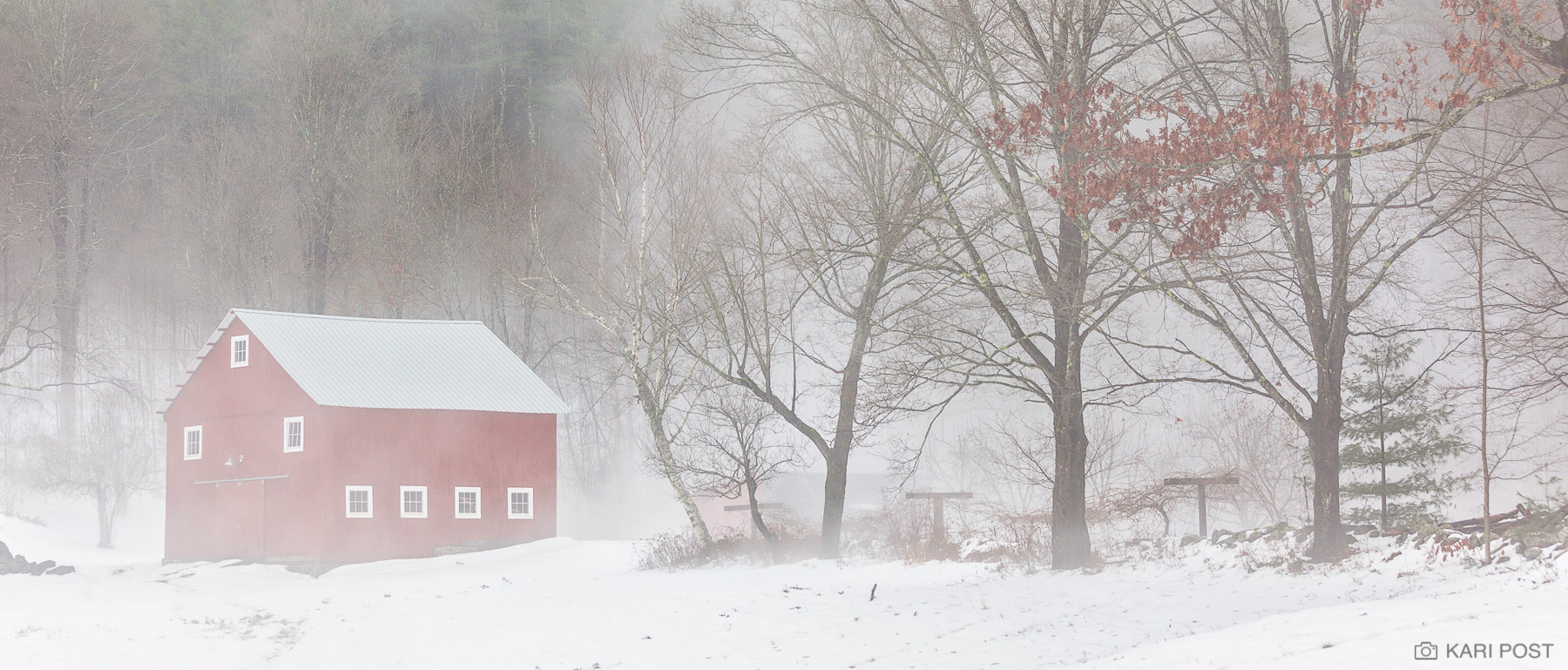 Fog shrouds a barn and trees as unseasonably warm temperatures cause the snow to melt in this rural New England winter scene.