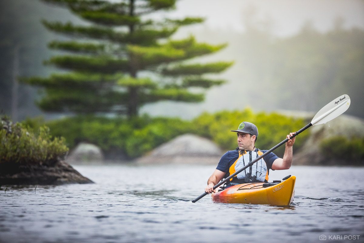 A male kayaker explores a quiet New Hampshire pond on an overcast summer morning.