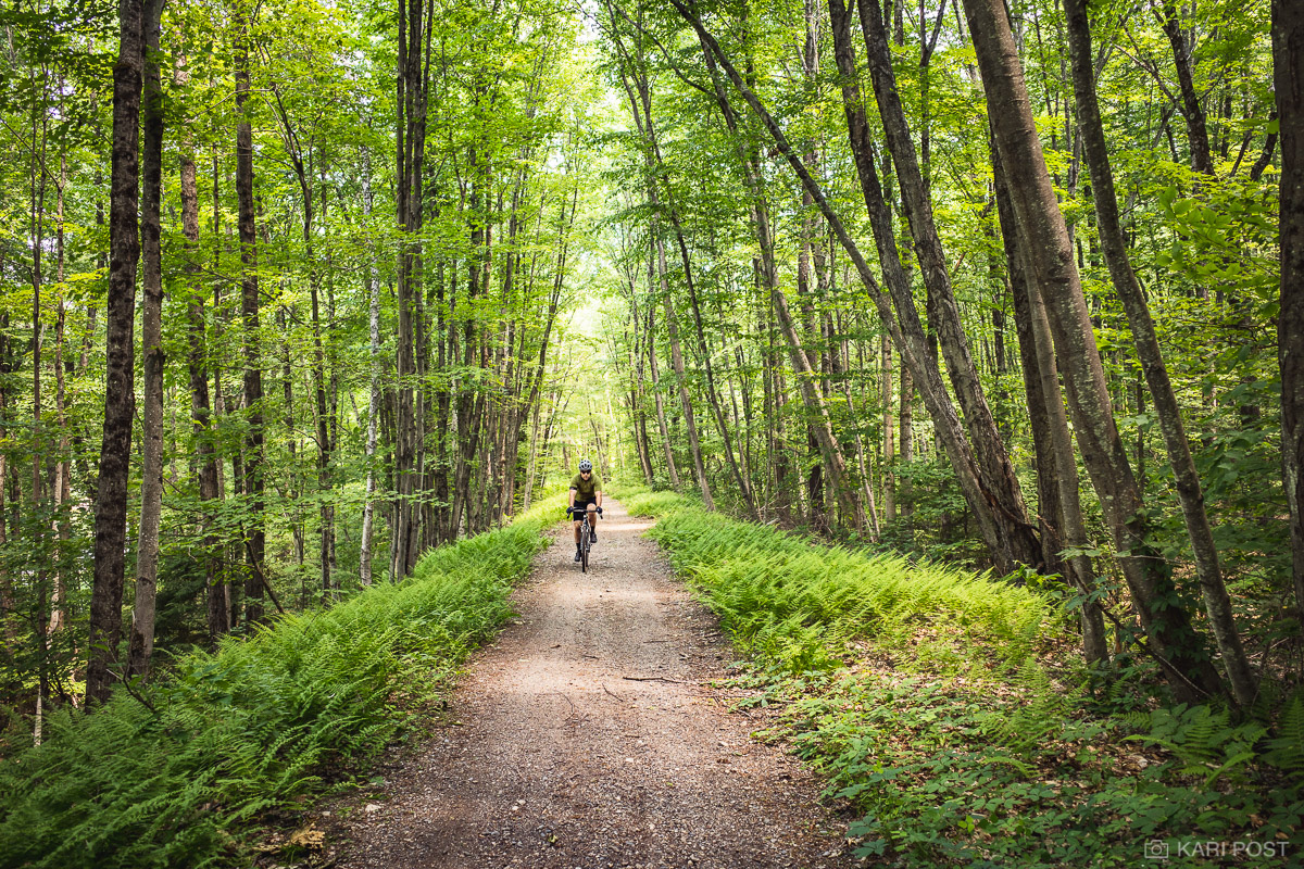 A male cyclist rides along the Cheshire Rail Trail in southwestern New Hampshire.