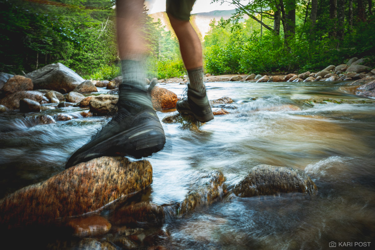 A hiker steps from rock to rock while crossing a small stream in the Pemigawassett Wilderness in New Hampshire's White Mountain...