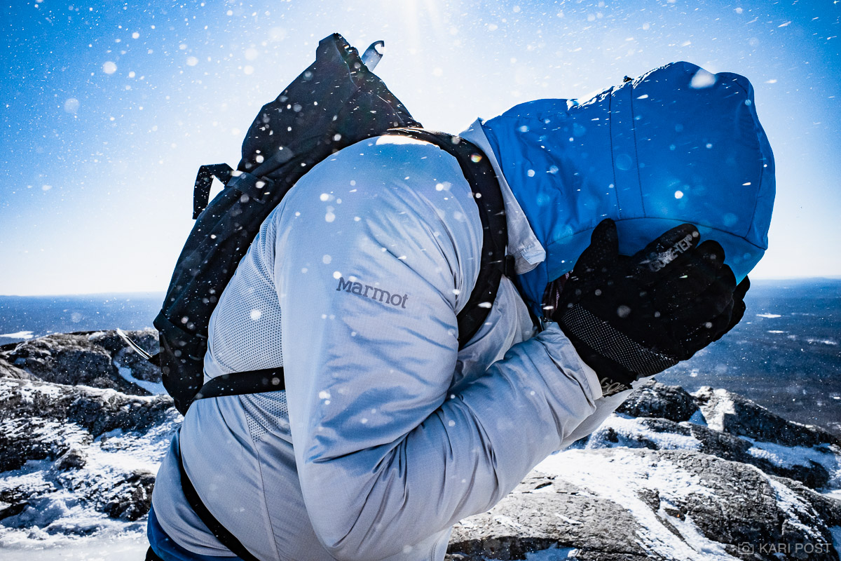 A hiker attempts to cover his face from blowing snow atop Mount Monadnock, the most hiked mountain in the United States, on a...