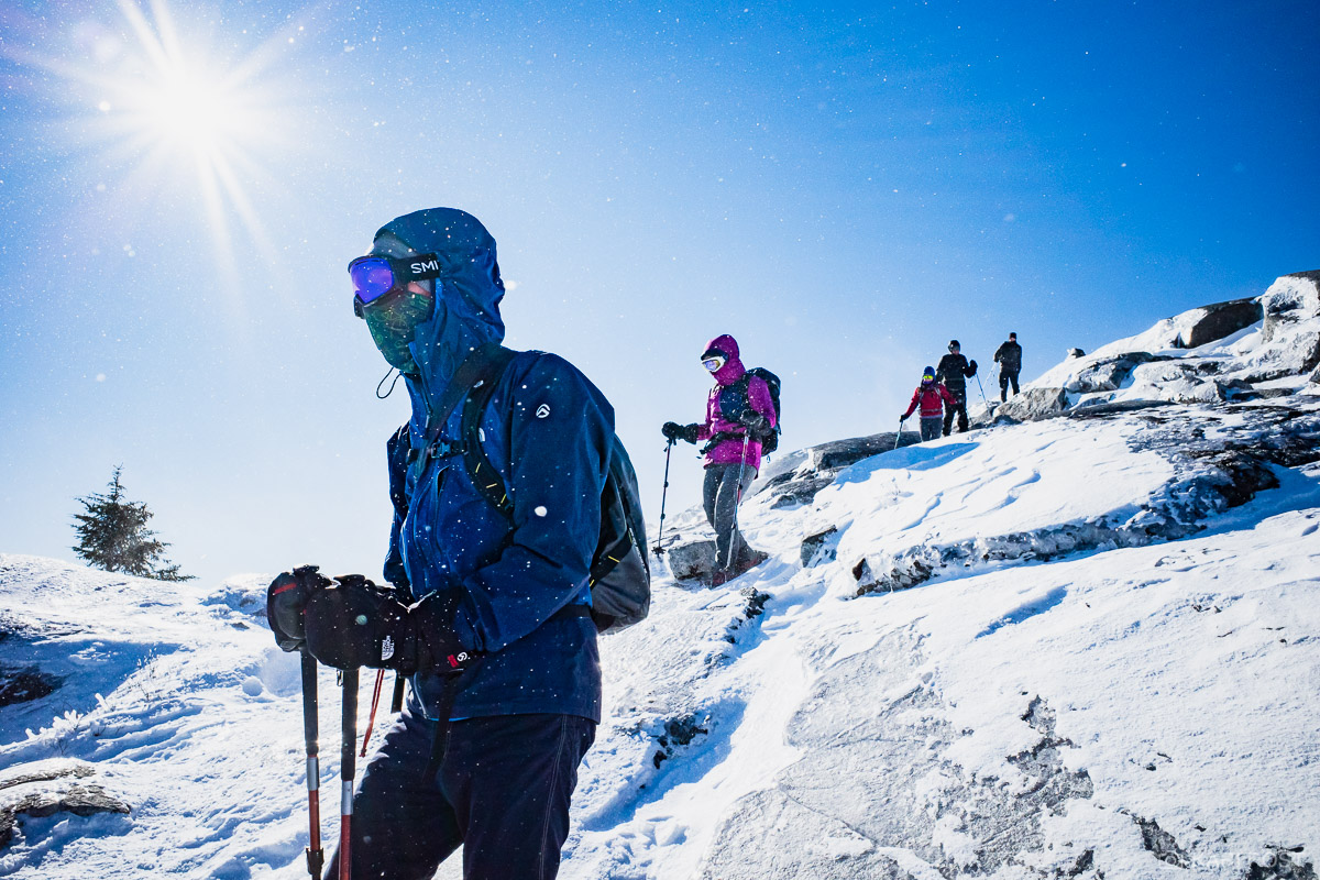 Hikers make their way down Mount Monadnock as snow blows on a bluebird winter day.