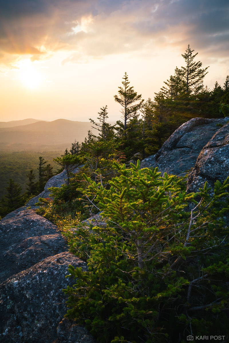 The sun dips below clouds just above the mountain horizon on a hazy summer day on Bald Mountain in Franconia Notch, White Mountain...